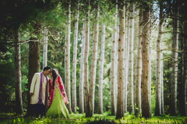 Indian couple portrait outdoors with tall trees