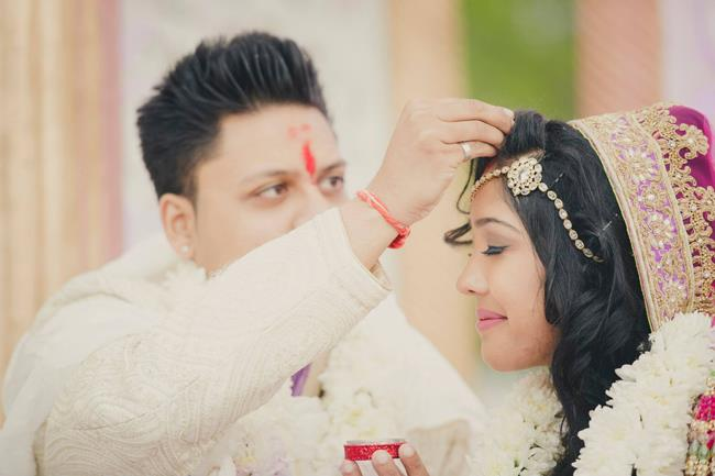 Indian groom applying sindoor on bride in Hindu wedding